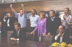 Prime Minister David Cameron of the United Kingdom, President Barack Obama, Chancellor Angela Merkel of Germany, José Manuel Barroso, President of the European Commission, President François Hollande of France and others watch the overtime shootout of the Chelsea vs. Bayern Munich Champions League final, in the Laurel Cabin conference room during the G8 Summit at Camp David.