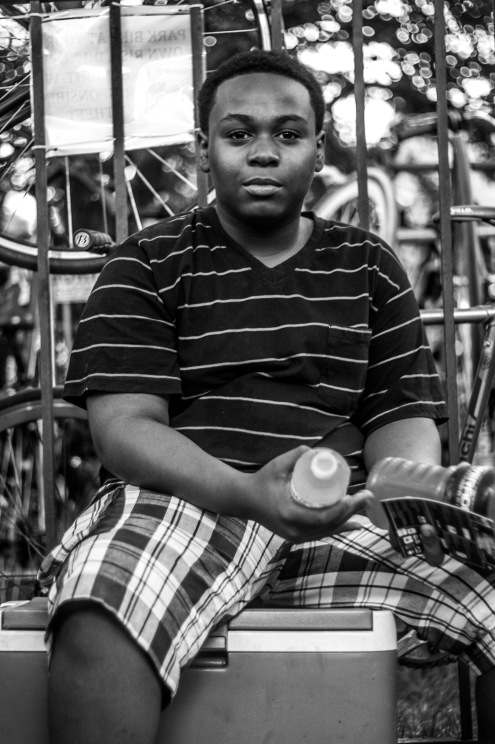 """Young Hawkers of Chicago"" Another young boy hustling, however, alongside his older sister and siblings on the edge of the park. He was timid of conversation - and rightfully so. I realized after walking away that I, in fact, cut into his hustling time. The term ""everybody needs to eat"" took on a new meaning after that moment."